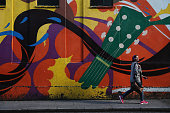 A woman walks past street art in the Temple Bar area on October 23 2013 in Dublin Ireland Dublin is the capital city of The Republic of Ireland...
