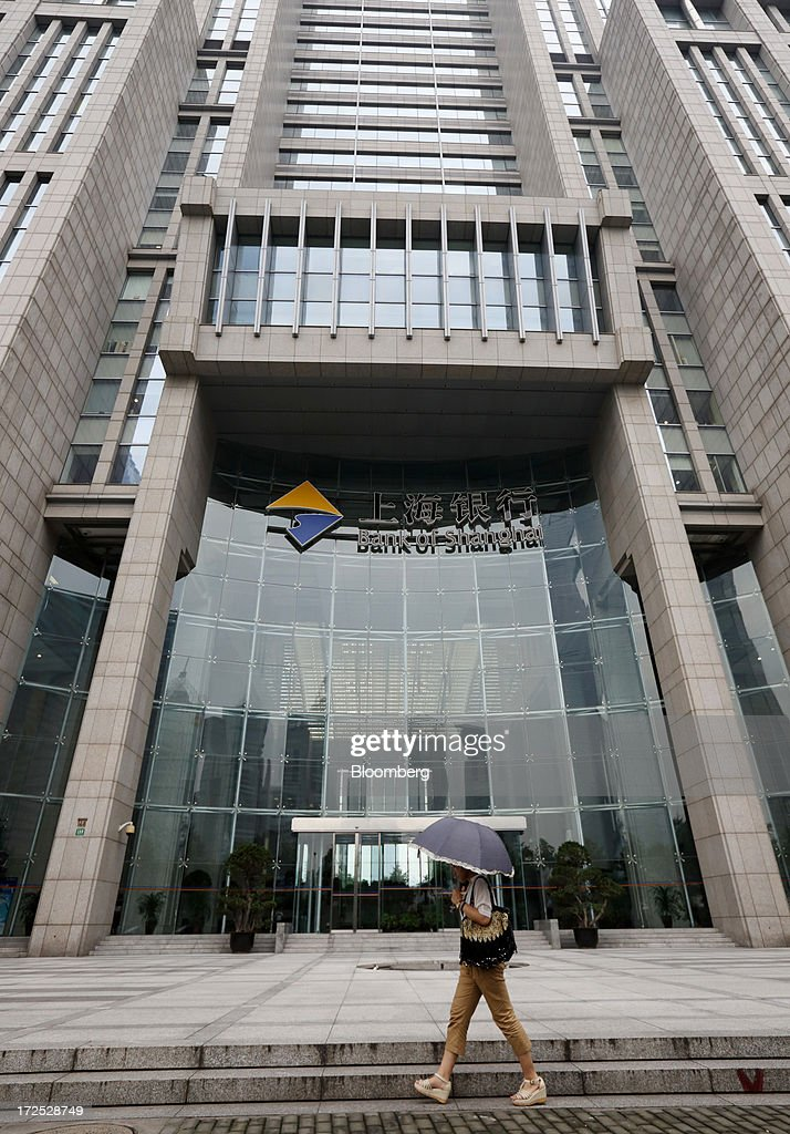 A woman walks past the Bank of Shanghai Co. headquarters in Shanghai, China, on Monday, July 1, 2013. Chinese banks' valuations are close to their lowest on record as the nation's interbank funding crisis exacerbated investors' concern that earnings growth will stall and defaults may surge as the economy slows. Photographer: Tomohiro Ohsumi/Bloomberg via Getty Images