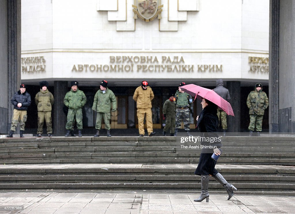 A woman walks past the Crimean Parliament building where cossacks stand guard on March 7, 2014 in Simferopol, Ukraine. Russian Cossacks, some heavily armed, have taken up guard duties at road checkpoints, border crossings and other key facilities that were previously guarded by local, pro-Russian militants across Crimea in recent days. The Crimean Parliament voted yesterday to hold a referendum on March 16 to determine whether Crimea shall secede from Ukraine and join Russia.
