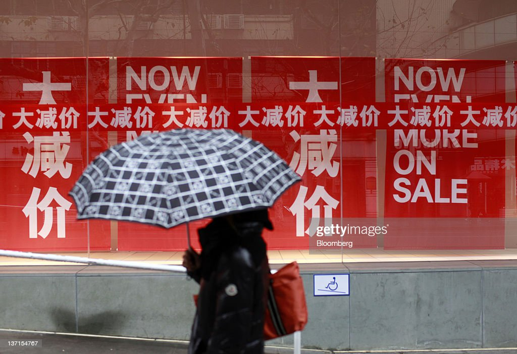 A woman walks past the display window of a clothing store in Shanghai, China, on Sunday, Jan. 15, 2012. China's economy probably grew the least in 10 quarters in the last three months of 2011 and may cool further as export demand slumps and officials prolong a campaign against property bubbles. Photographer: Qilai Shen/Bloomberg via Getty Images