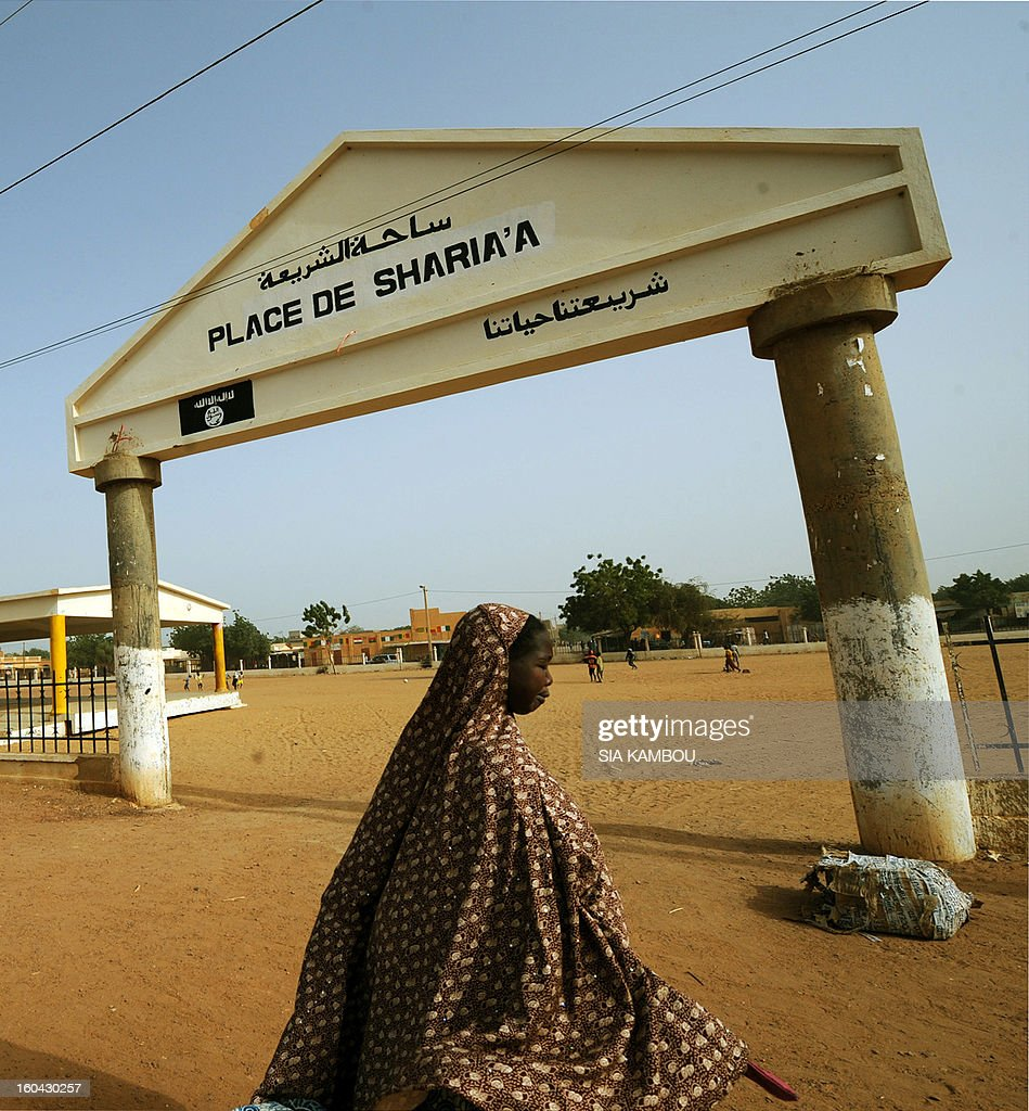 A woman walks past the entrance of Sharia Plaza on January 31, 2013 in the northern Malian city of Gao, where Islamists of the Movement for Oneness and Jihad in West Africa (MUJAO), who controlled the city, applied Islamic sharia law with public punishments, including stoning and amputation of limbs. Gao was retaken on January 26 by French and Malian troops in a major boost to the French-led offensive against the Al Qaeda-linked rebels, who have been holding Mali's vast desert north since last April. FP