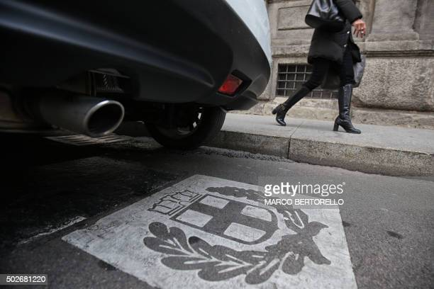 A woman walks past the exhaust pipe of a car and the symbol of Milan on December 28 2015 Drivers in Milan will face a limit on daytime travel three...