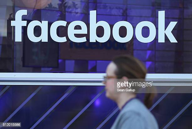 A woman walks past the Facebook logo at the Facebook Innovation Hub on February 24 2016 in Berlin Germany The Facebook Innovation Hub is a temporary...