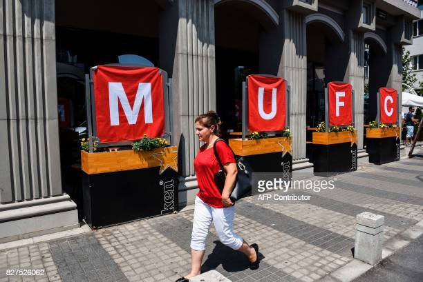 A woman walks past the flags depicting the Manchester United club in Skopje on August 8 2017 ahead of the UEFA Super Cup football match between Real...