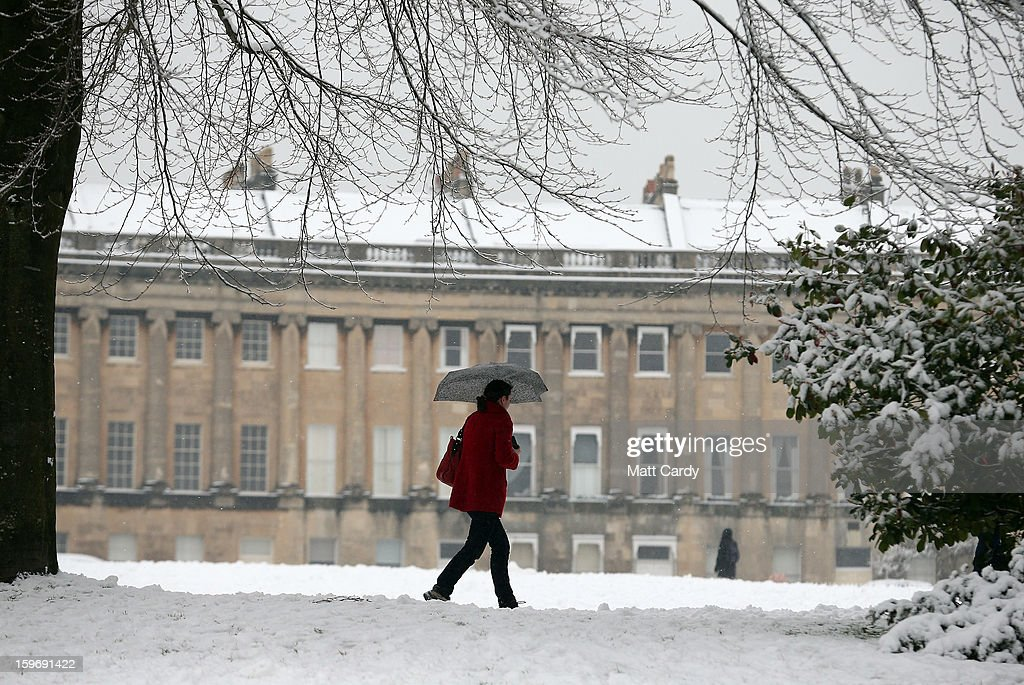 A woman walks past the front of the Royal Crescent overlooking Victoria Park on January 18, 2013 in Bath, England. Heavy snow is bringing widespread disruption to many parts of the UK.