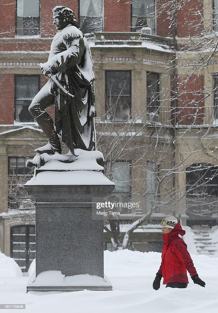 A woman walks past the General John Glover statue on the Commonwealth Avenue Mall following a powerful blizzard on February 9, 2013 in Boston, Massachusetts. The storm knocked out power to 650,000 and dumped more than two feet of snow in parts of New England.
