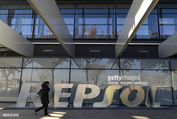 A woman walks past the headquarters of Spanish oil company Repsol in Madrid on December 16 2014 Spanish oil giant Repsol said on December 16 2014 it...