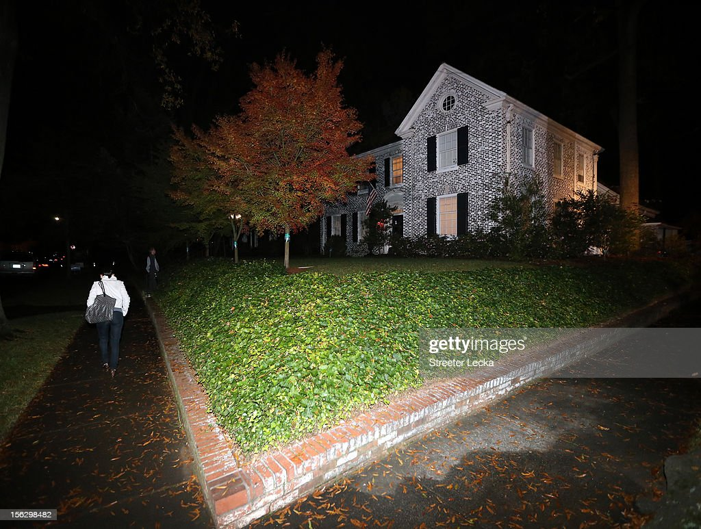 A woman walks past the home of Paula Broadwell after a FBI search on November 13, 2012 in the Dilworth neighborhood of Charlotte, North Carolina. Broadwell is the recently discovered mistress of CIA Director David Petraeus, which has led to his resignation in light of the scandal.