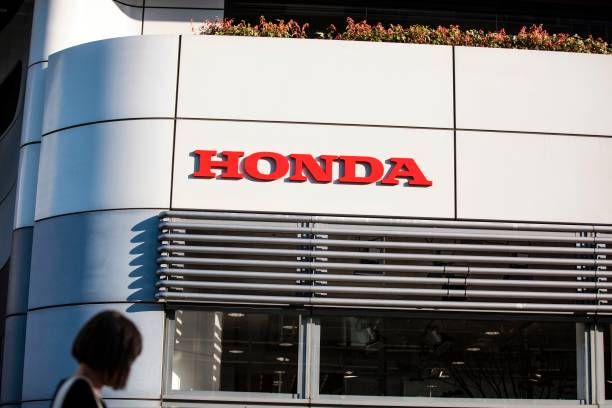 A Woman Walks Past The Honda Headquarters Building In Tokyo On April 28 2017 Said Its Annual Net Profit Jumped 79 Percent Reduction