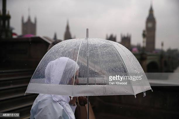 A woman walks past the Houses of Parliament in heavy rain on August 13 2015 in London England The Met Office has issued an amber warning for heavy...