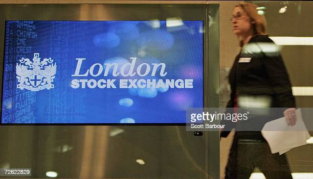 A woman walks past the logo of the London Stock Exchange as it is displayed on a screen in the foyer of the London Stock Exchange on November 22 2006...