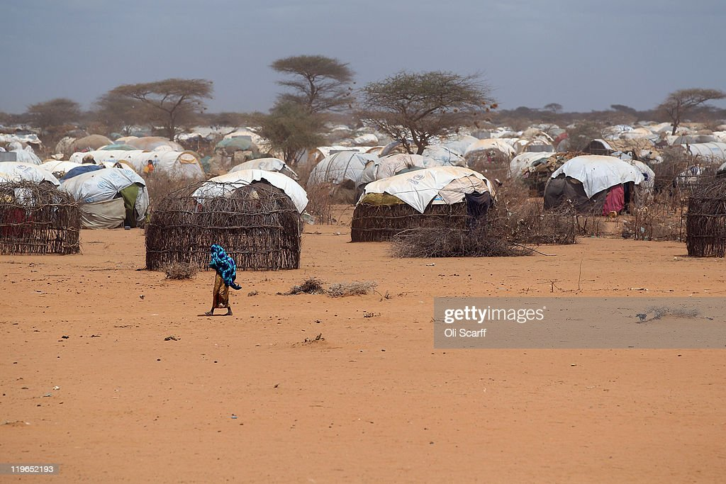 A woman walks past the makeshift huts of newly arrived Somalian refugees on the edge of the Dagahaley refugee camp which makes up part of the giant...