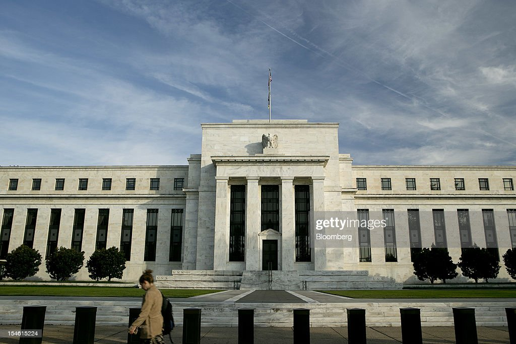 A woman walks past the Marriner S. Eccles Federal Reserve building in Washington, D.C., U.S., on Tuesday, Oct. 23, 2012. Federal Reserve Chairman Ben S. Bernanke, who is seeking to spur the economy with a third round of so-called quantitative easing, has said his stimulus works by lowering borrowing costs and encouraging investors to seek higher-yielding assets. Photographer: Andrew Harrer/Bloomberg via Getty Images