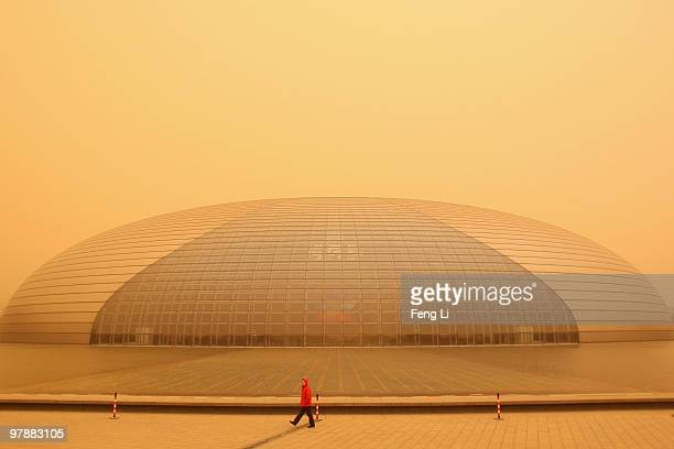 A woman walks past the National Grand Theater in a sandstorm on March 20 2010 in Beijing China The severe sandstorm which had buffeted northwestern...