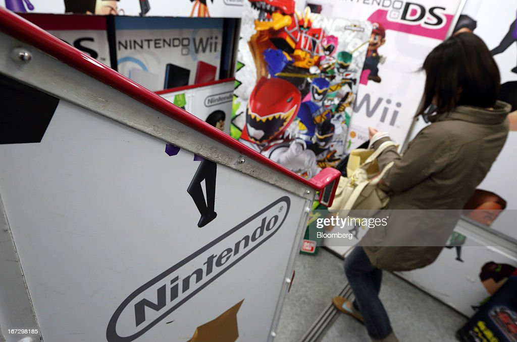 A woman walks past the Nintendo Co. logo displayed at an electronics store in Tokyo, Japan, on Tuesday, April 23, 2013. Nintendo, the world's largest maker of video-game machines, will announce earnings on April 24. Photographer: Tomohiro Ohsumi/Bloomberg via Getty Images