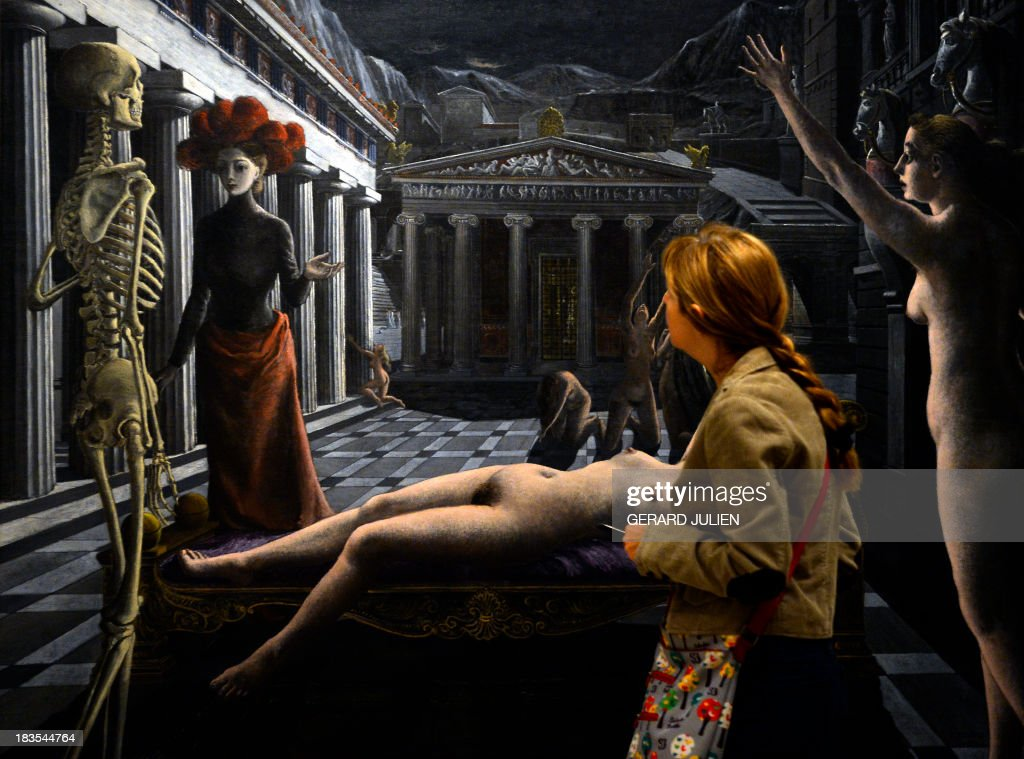 A woman walks past the painting 'La Venus endormie' by Paul Delvaux during the exhibition entitled 'Surrealism and the Dream' at the Thyssen-Bornemisza museum in Madrid, on October 7, 2013.