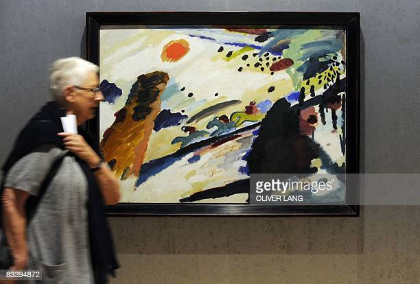 A woman walks past the painting 'Romantische Landschaft' of Russian painter Wassily Kandinsky during the press preview of the exhibition 'Kandinsky...