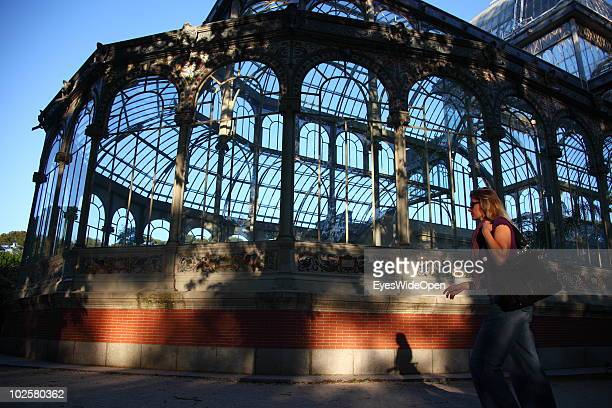 A woman walks past the Palacio de Cristal called the Crystal Palace or Glass Palace in the famous Parque Del Retiro in Madrid on May 20 2010 in...