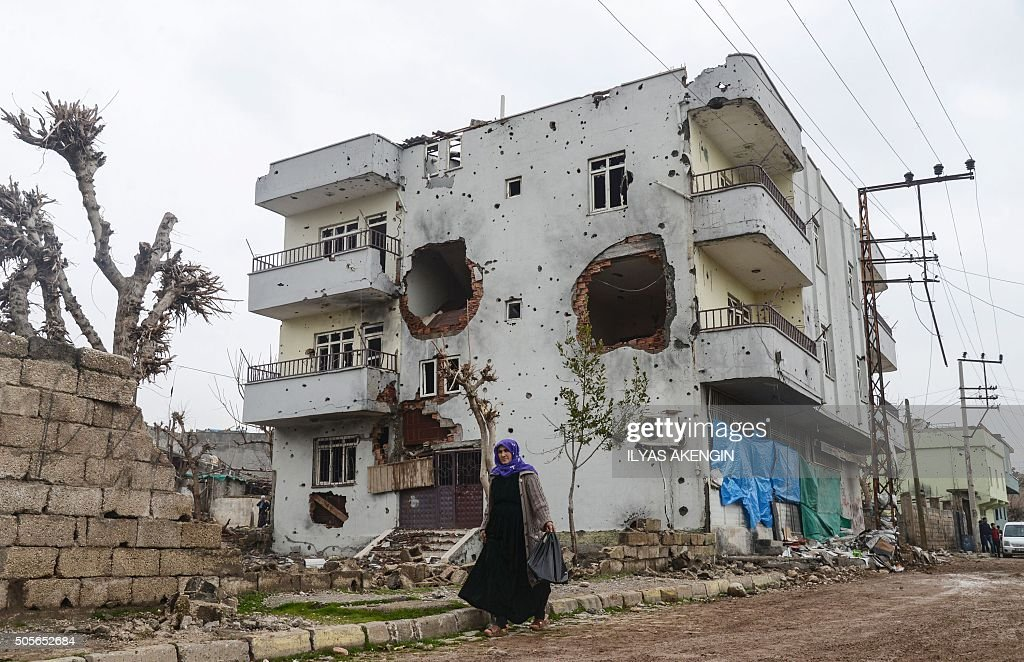TOPSHOT A woman walks past the ruins of a building as curfew ends during daylight in the town of Silopi on January 19 2016 Turkey is waging an allout...