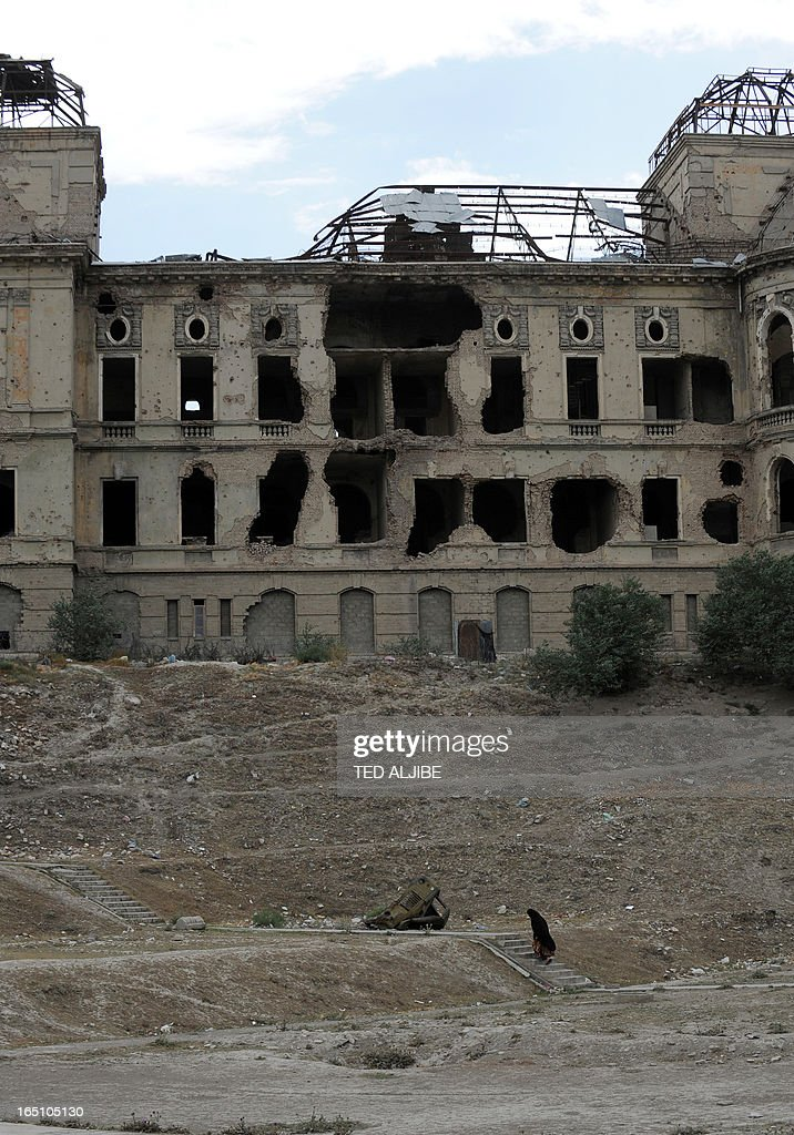 A woman walks past the ruins of Darulaman palace, the former residence of Afghan King Amanullah who reigned from 1920 to 1929, in Kabul on June 12, 2011. From a position of lonely authority, President Barack Obama faces wrenching political and even moral dilemmas as he plots a troop drawdown in Afghanistan due to begin next month. AFP PHOTO/TED ALJIBE