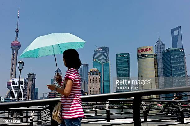 A woman walks past the skyline of Shanghai's financial district on June 2 2010 Chinese shares fell 161 percent in afternoon trading led by falls in...