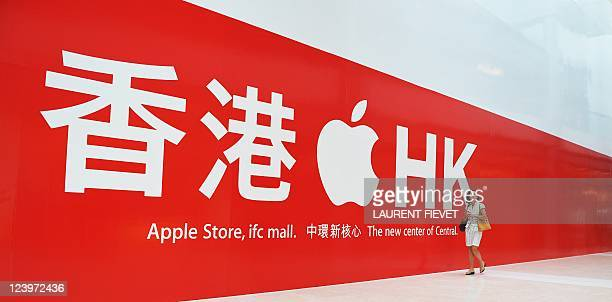 A woman walks past the soon to open new Apple store in Hong Kong on September 7 2011 Apple plans to open its first store in Hong Kong and another in...