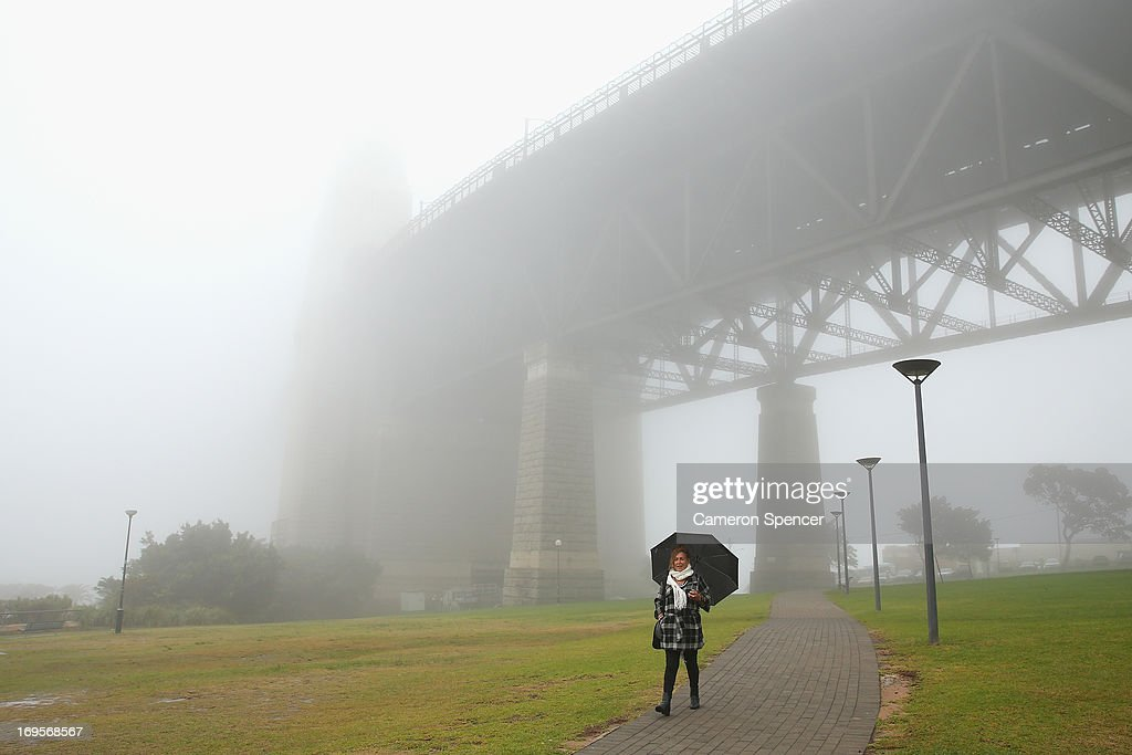 A woman walks past the Sydney Harbour Bridge as a blanket of fog covers Sydney Harbour on May 28, 2013 in Sydney, Australia. Fog covered the city today resulting in flight and ferry cancellations and reduced visibility on roads.