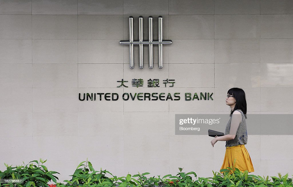 A woman walks past the United Overseas Bank Ltd. (UOB) logo displayed outside a branch in Singapore, on Wednesday, Feb. 27, 2013. UOB is scheduled to announce full year results today. Photographer: Munshi Ahmed/Bloomberg via Getty Images
