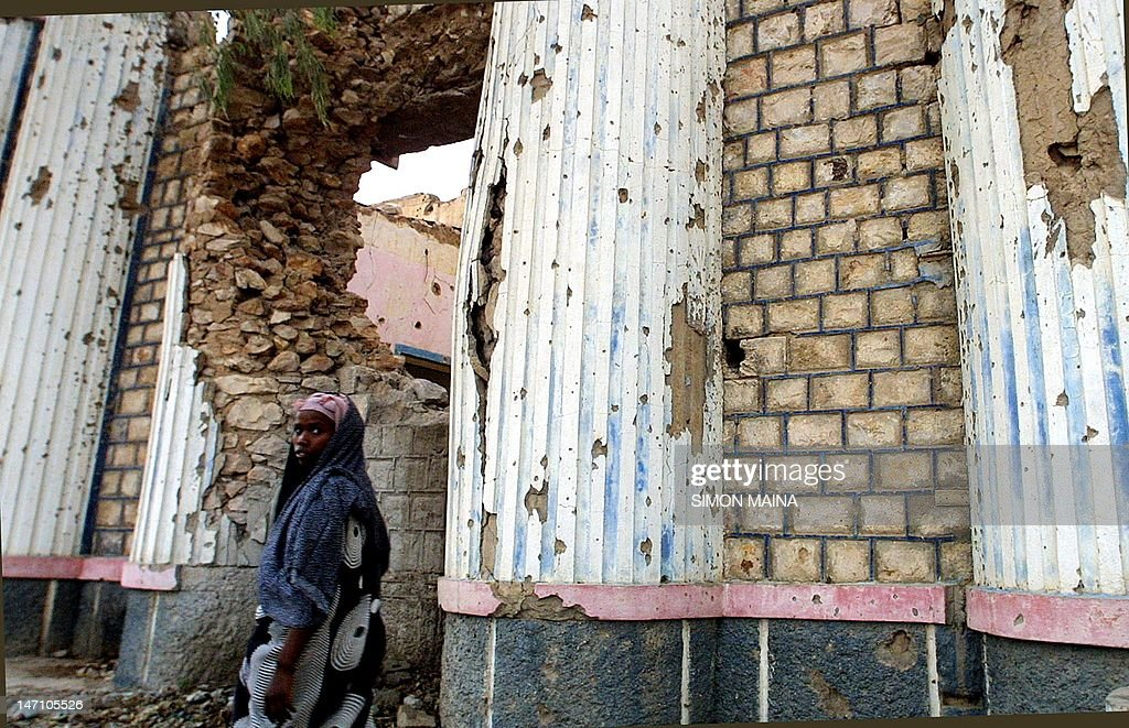 A woman walks past the wall of what used to be a national theatre in Hargeisa that was destroyed by artillery bombardment by Somali National Movement...