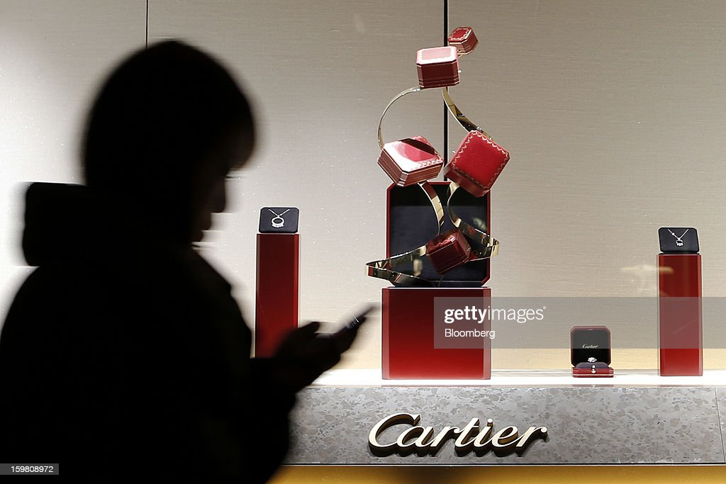 A woman walks past the window of a Cie. Financiere Richemont SA's Cartier brand store in the Ginza district of Tokyo, Japan, on Sunday, Jan. 20, 2013. Japan's consumer prices excluding fresh food, a benchmark monitored by the central bank, haven't advanced 2 percent for any year since 1997, when a national sales tax was increased. Photographer: Kiyoshi Ota/Bloomberg via Getty Images