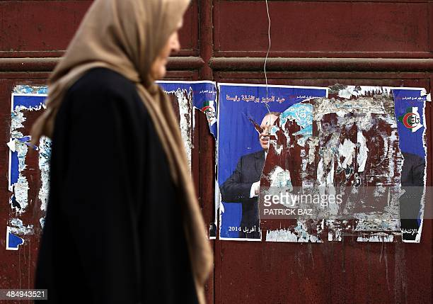 A woman walks past torn posters of current Algerian president Abdelaziz Bouteflika who is running for reelection in the city of Borj alBahri 24km...