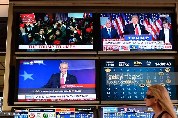 A woman walks past TV monitors displaying results of the US presidential elections at an outdoor cafe in Athens on November 9 2016 Donald Trump has...
