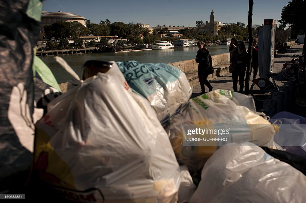 A woman walks past uncollected rubbish on a riverbank of Sevilla on February 4, 2013. Rubbish collectors have been on strike in the municipality of Sevilla to protest against the austerity cuts imposed by the town hall.