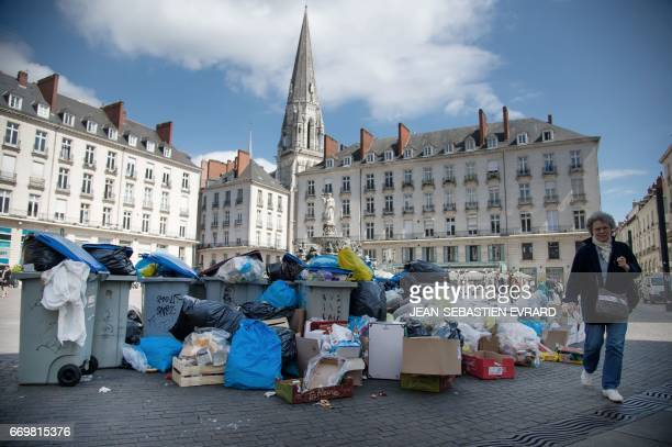 A woman walks past uncollected trash amid a strike by garbage collectors in Nantes western France on April 18 2017 / AFP PHOTO / JEANSEBASTIEN EVRARD