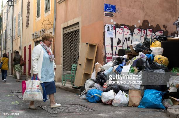 A woman walks past uncollected trash during a strike by refuse collectors on October 18 in the Panier district of Marseille southern France / AFP...
