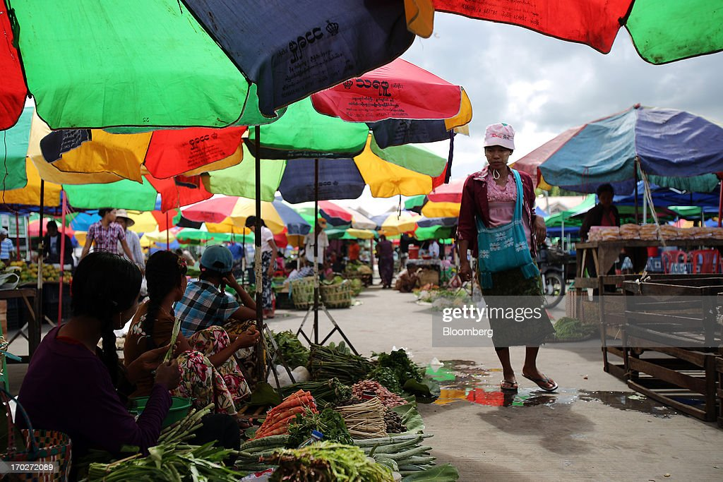 A woman walks past vegetable stalls at a market in Naypyidaw, Myanmar, on Friday, June 7, 2013. President Thein Sein has allowed more political freedom and loosened economic controls since coming to power two years ago, prompting the U.S. and other nations to ease sanctions. Photographer: Dario Pignatelli/Bloomberg via Getty Images