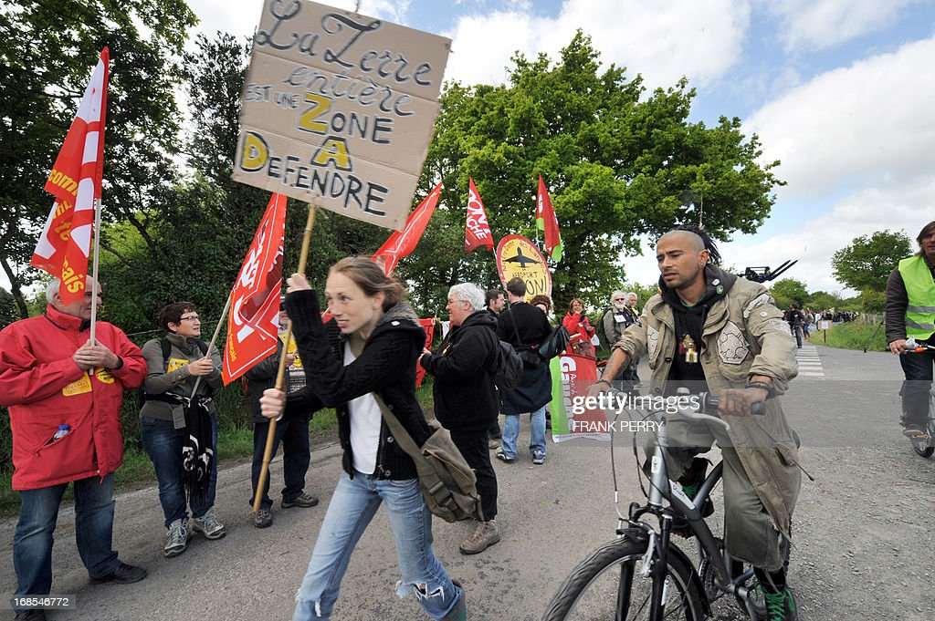 A woman walks past with a sign reading 'The entire Earth is a Zone to Protect' as activists of the French left-wing 'Front de Gauche' party hold hands and form a human chain during a protest against the construction of a new airport in Notre-Dame des Landes, on May 11, 2013. Several thousand protesters, at least 5 000 according to the local police department, gathered