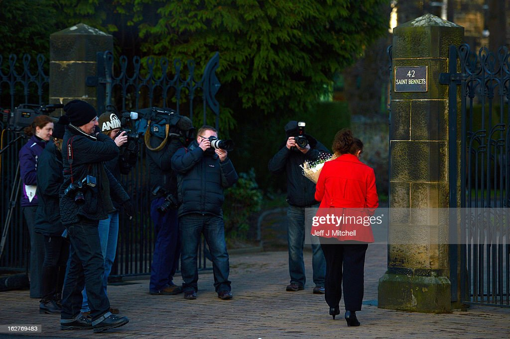 A woman walks past with flowers as members of the press gather at the official residence former Cardinal Keith O'Brien on February 26, 2013 in Edinburgh, Scotland. The former Cardinal Keith O'Brien, was Britain's most senior Roman Catholic, has resigned following allegations from three priests and one former priest of inappropriate behavior.