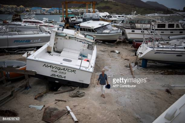 A woman walks past wrecked boats in Geminga shipyard in Marigot on September 9 2017 in SaintMartin island devastated by Irma hurricane Officials on...