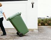 Woman Walks Pulling a Bin