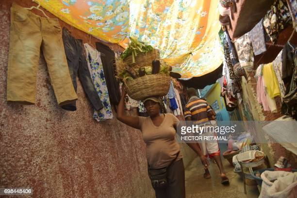 A woman walks selling vegetables on the streets of Jalousie neighborhood in the commune of Petion Ville PortauPrince on June 20 2017 / AFP PHOTO /...