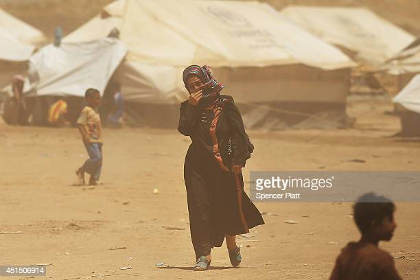 A woman walks through a dust storm at the Khazair displacement camp for those caughtup in the fighting in and around the city of Mosul on June 30...