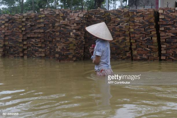 TOPSHOT A woman walks through a flooded alley at Tat Dong village in Hanoi's outskirt district of Chuong My on October 16 2017 Vietnam is bracing for...