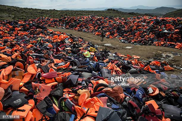 A woman walks through a pile of thousands of discarded life vests dumped in a valley in hills above the town on March 27 2016 in Mithymna Greece New...