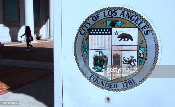 A woman walks through a plaza in front of City Hall in Los Angeles California on August 22 2017 The city of Los Angeles has sued the US Justice...