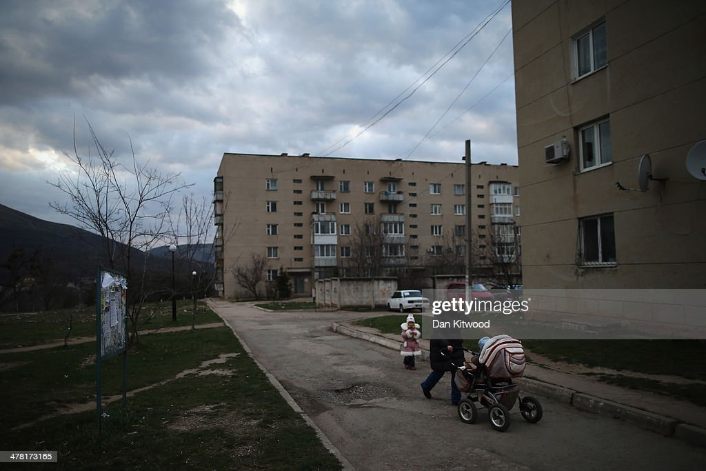 A woman walks through a residential estate next to the perimeter of a Ukrainian military base on March 12, 2014 in Simferopol, Ukraine. As the standoff between the Russian military and Ukrainian forces continues in Ukraine's Crimean peninsula, world leaders are pushing for a diplomatic solution to the escalating situation. Crimean citizens will vote in a referendum on 16 March on whether to become part of the Russian federation.