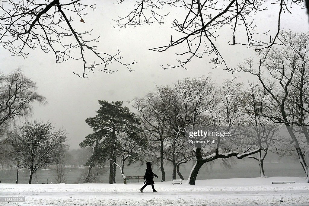 A woman walks through a snow-shrouded park on March 8, 2013 in the Brooklyn borough of New York City. As a week-old storm slowly moves out to sea, the New York City area is expecting 1 to 3 inches of snow with more in areas north and west of the city. The storm has caused flight delays at area airports and numerous schools have delayed start times.