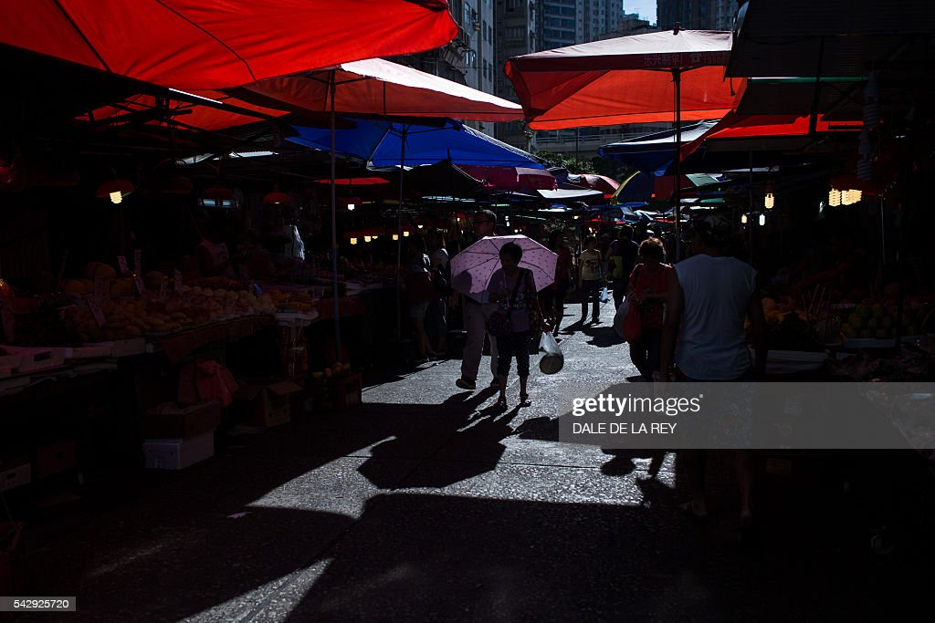 A woman walks through a traditional wet market in Hong Kong on June 25, 2016. / AFP / DALE