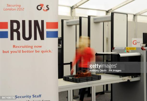 A woman walks through an xray machine as Olympic Games security company G4S trains its new recruits for the London 2012 Olympic Games Straford London