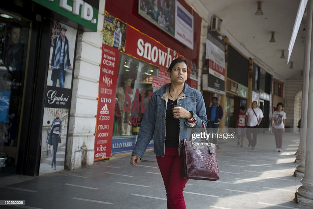 A woman walks through Connaught Place in New Delhi, India, on Saturday, Feb. 23, 2013. Finance Minister Palaniappan Chidambaram, who will present his annual budget to parliament on Feb. 28, will seek to narrow the shortfall to 4.8 percent of gross domestic product in the year starting April, from this year's goal of 5.3 percent, according to a Bloomberg survey of analysts and investors. Photographer: Brent Lewin/Bloomberg via Getty Images